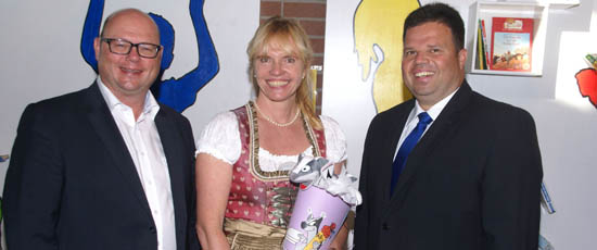 Harald Mundl and Martin Hofmann presenting a large cornet of cardboard filled with sweets and little presents for first day at school with Frechdachs on it to Alexandra Wolff for taking office principal at primary school Weichs